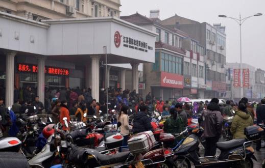 People gather in front of a branch of Jiangsu Sheyang Rural Commercial Bank, in Yancheng